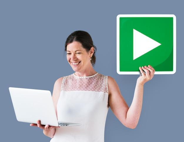 Mulher segura, um, jogue botão, e, um, laptop Foto gratuita