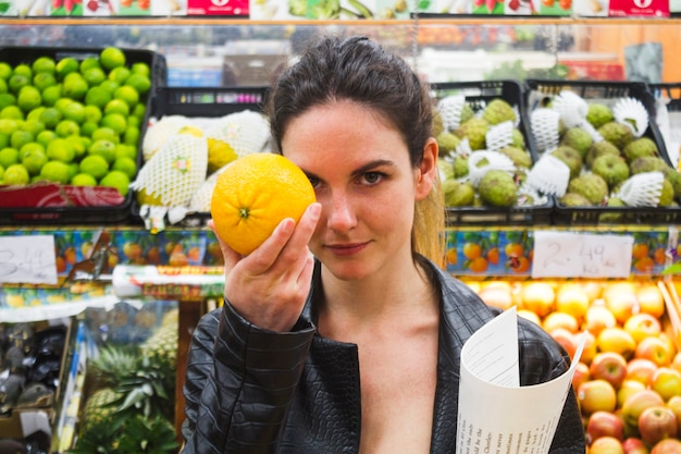 Mulher segura, um, laranja, em, um, mercearia Foto gratuita