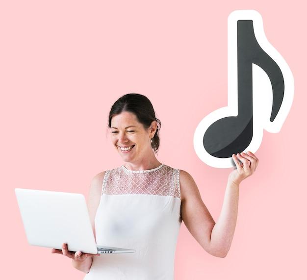 Mulher segura, um, nota musical, e, um, laptop Foto gratuita