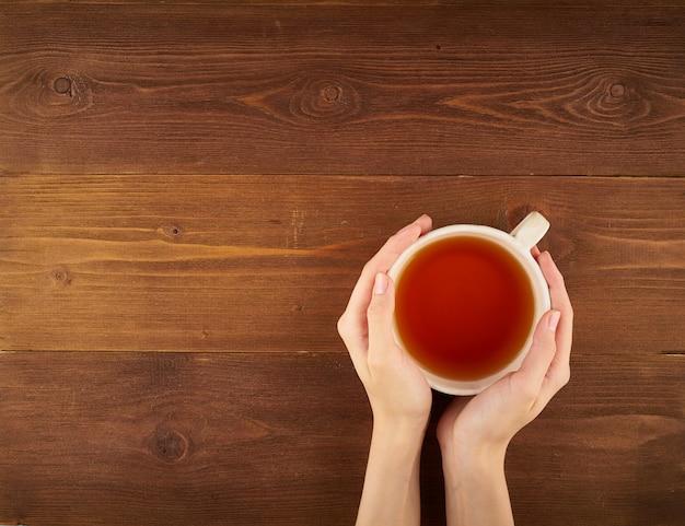 Mulher segura, um, xícara chá, ligado, madeira escura Foto Premium