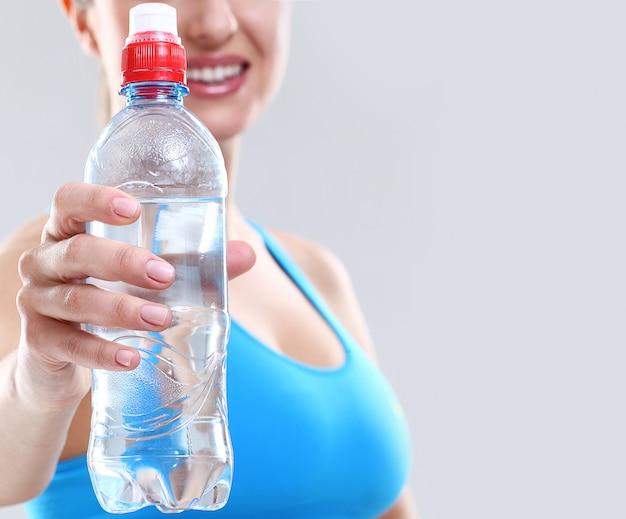 Mulher segura uma garrafa de água Foto gratuita