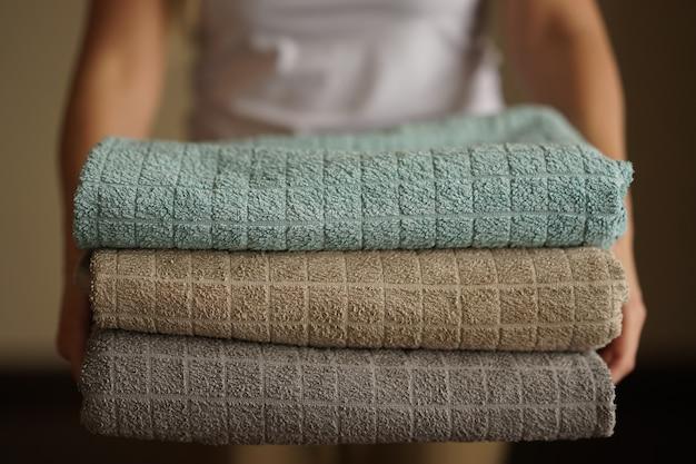 Mulher segura uma pilha de toalhas turcas neutras multicoloridas com as duas mãos Foto Premium