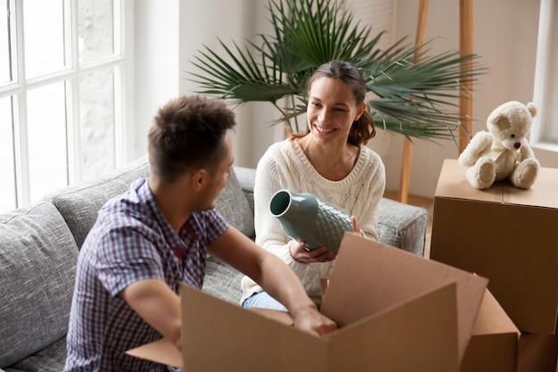 Mulher segura, vaso, ajudando, homem, caixas embalagem, ligado, dia móvel Foto gratuita