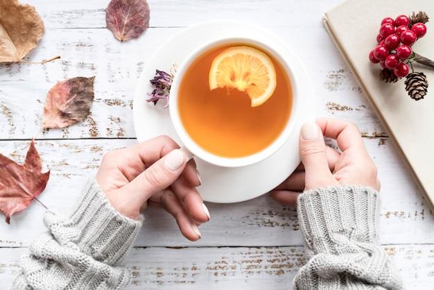 Mulher segura, xícara chá, entre, folhas Foto gratuita