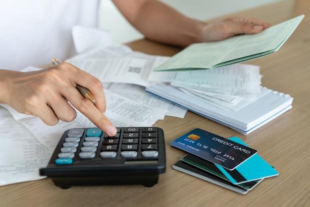 Mulher segurando a caderneta da conta poupança e usando a calculadora, a conta e o conceito de economia. Foto Premium