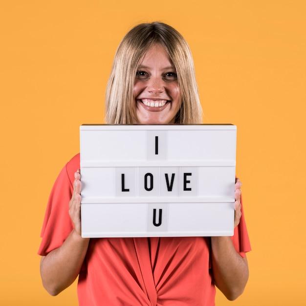 Mulher segurando a caixa de luz com eu te amo texto contra pano de fundo de estúdio simples Foto gratuita