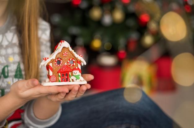 Mulher segurando a casa de gengibre de natal Foto Premium