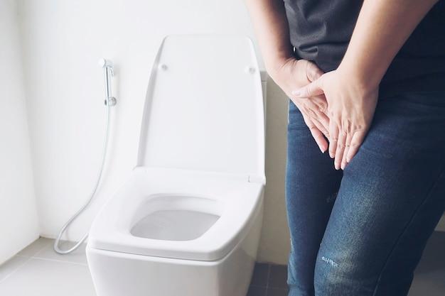 Mulher segurando a mão perto de vaso sanitário - conceito de problema de saúde Foto gratuita