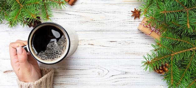 Mulher segurando a xícara de café quente na mesa de madeira rústica. mãos na camisola quente com caneca, manhã de inverno ou conceito de natal Foto Premium