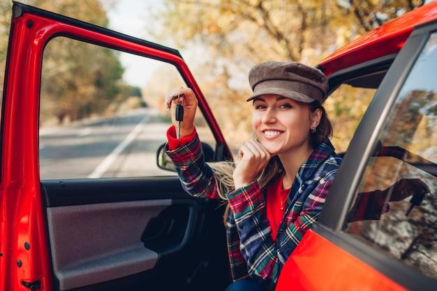 Mulher segurando as chaves do carro novo. o comprador feliz comprou o automóvel vermelho. motorista, olhando para a câmera, sentado no automóvel Foto Premium