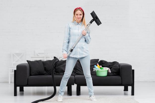 Mulher segurando aspirador Foto gratuita