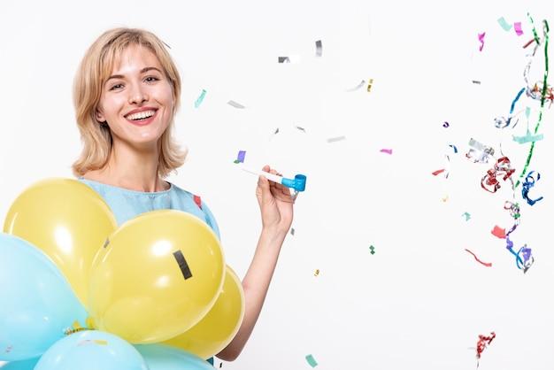 Mulher segurando balões rodeados de confete Foto gratuita