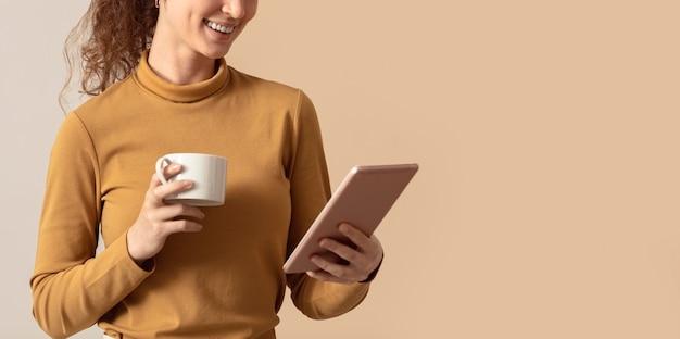 Mulher segurando café da manhã e usando tablet digital Foto gratuita