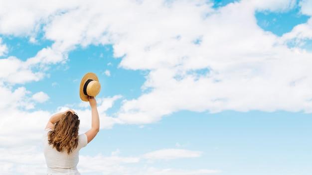 Mulher segurando chapéu admirando nuvens no céu Foto gratuita