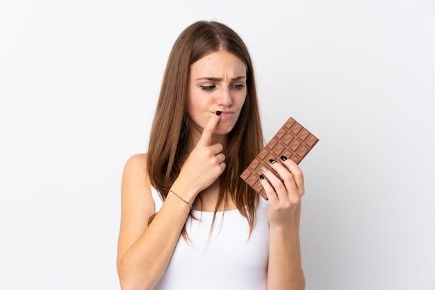 Mulher segurando chocolate sobre parede branca Foto Premium