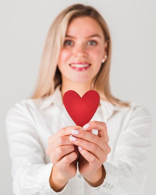 Mulher segurando coração para dia dos namorados Foto gratuita