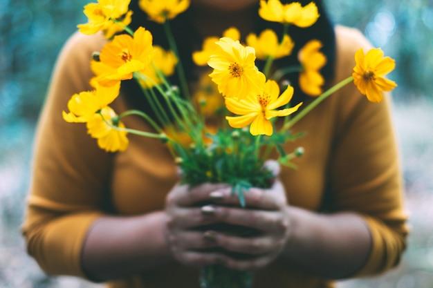 Mulher segurando cosmos amarelo flor na mão Foto Premium