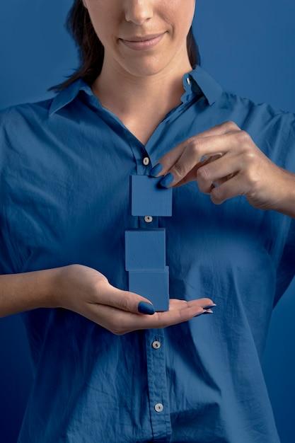 Mulher segurando cubos de cor azul clássico empilhados Foto gratuita