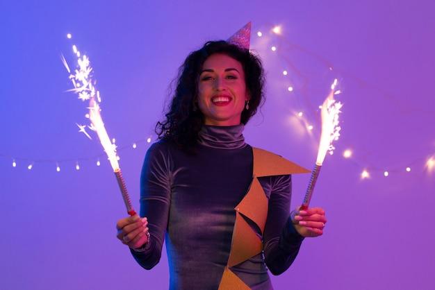 Mulher segurando diamante ardente festivo e se divertindo. Foto Premium