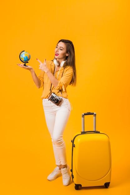 Mulher segurando e apontando para o globo com bagagem ao lado dela Foto gratuita