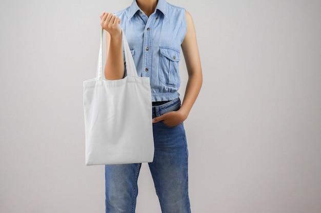 Mulher segurando eco saco de tecido isolar em fundo cinza Foto Premium