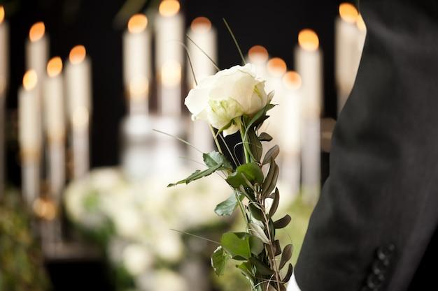 Mulher segurando flor branca no funeral Foto Premium