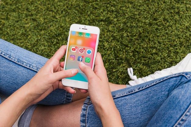 Mulher segurando móvel usando aplicativos de rede social Foto gratuita