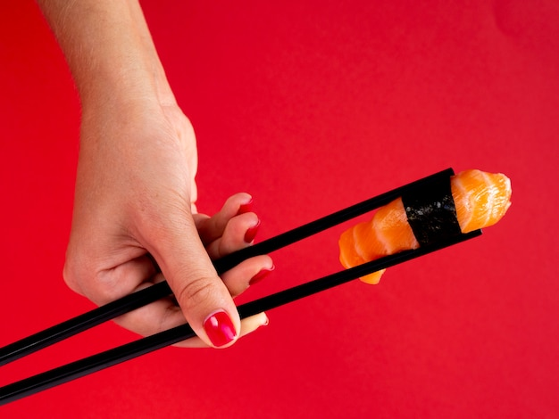Mulher segurando nos pauzinhos um sushi de salmão Foto gratuita