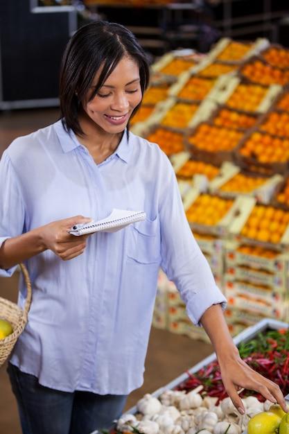 Mulher segurando o bloco de notas enquanto fazia compras Foto Premium