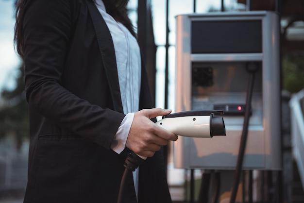 Mulher segurando o carregador do carro na estação de carregamento de veículos elétricos Foto gratuita