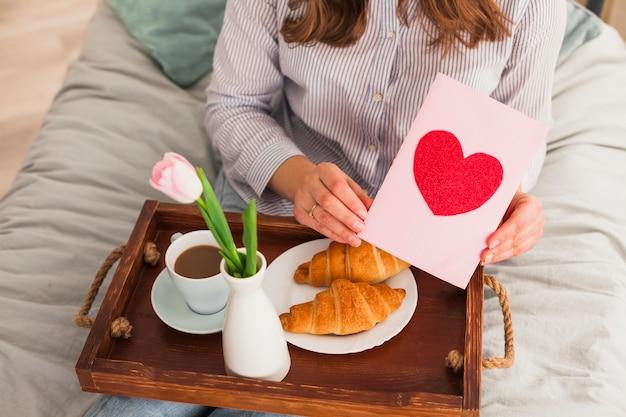 Mulher segurando o cartão com desenho de coração vermelho Foto gratuita