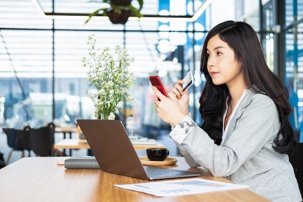 600611c46 mulher segurando o cartão de crédito e usando o site de compras de laptop e  smartphone