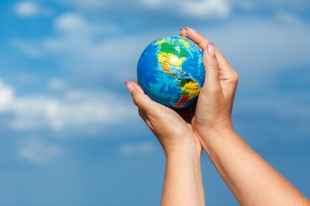 Mulher segurando o globo da terra em um fundo do mar. Foto Premium