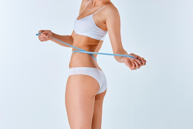 Mulher segurando o medidor medindo a forma perfeita de seu corpo bonito Foto gratuita