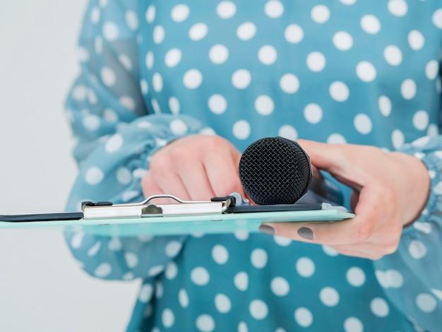 Mulher segurando o microfone e área de transferência Foto gratuita