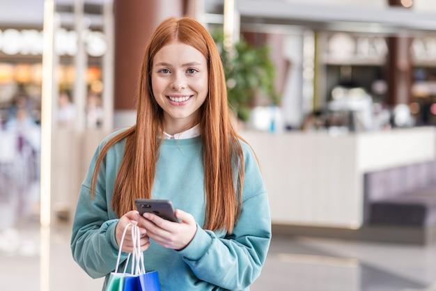 Mulher segurando o telefone e olhando para o fotógrafo Foto gratuita