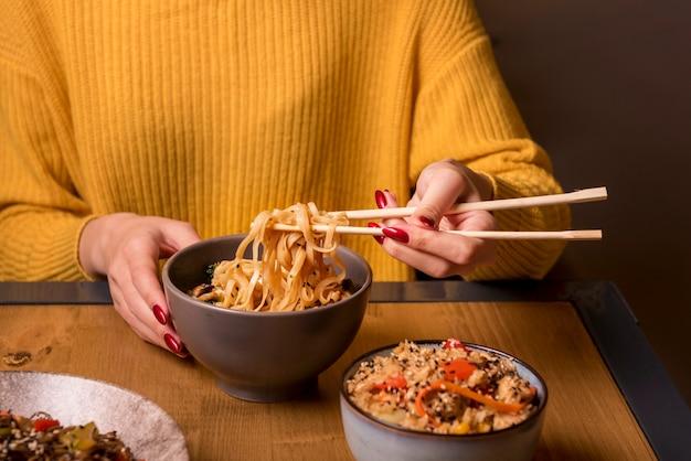 Mulher segurando os pauzinhos com macarrão na mesa Foto gratuita