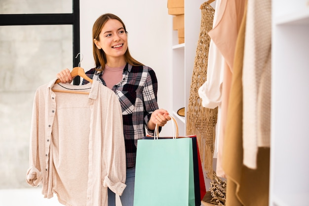Mulher segurando sacos de papel e olhando para um guarda-roupa Foto gratuita