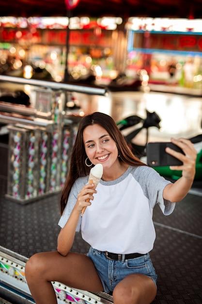 Mulher segurando sorvete tomando selfie Foto gratuita