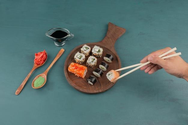 Mulher segurando sushi roll com pauzinhos na mesa azul com gengibre em conserva e molho de soja. Foto gratuita