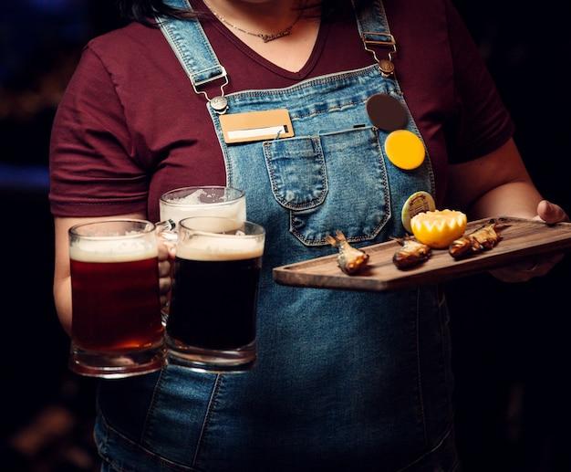 Mulher segurando três canecas de cerveja e prato de peixe defumado com limão Foto gratuita