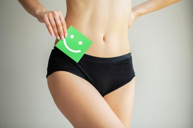 Mulher segurando um cartão verde com um sorriso feliz nas mãos Foto Premium