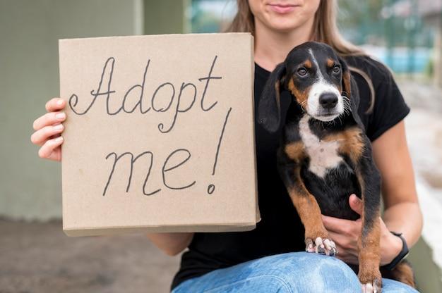 Mulher segurando um cartaz de adote-me e resgate o cachorro Foto gratuita