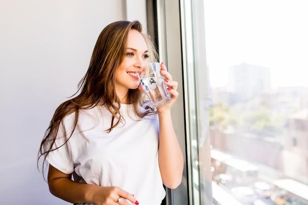 Mulher segurando um copo d'água enquanto olha pela janela - costas da silhueta de uma mulher Foto gratuita