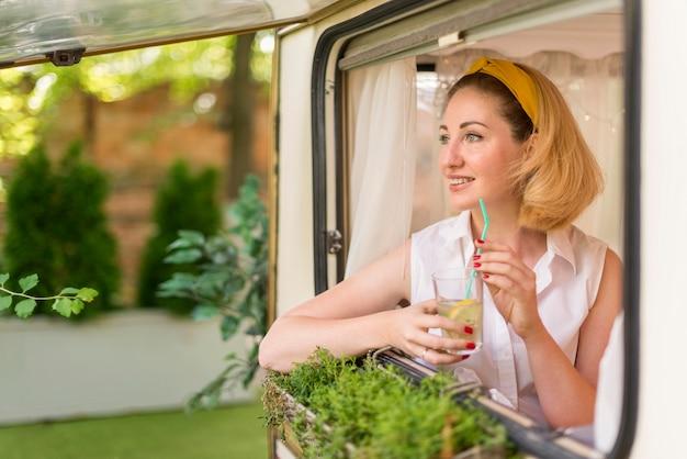 Mulher segurando um copo de limonada em um trailer com espaço de cópia Foto gratuita