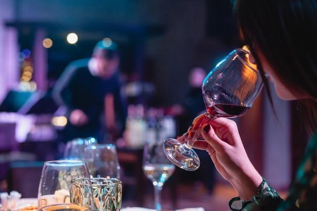Mulher segurando um copo de vinho tinto. jantar no restaurante, festa Foto Premium