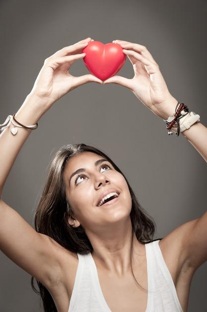 Mulher segurando um coração vermelho Foto Premium