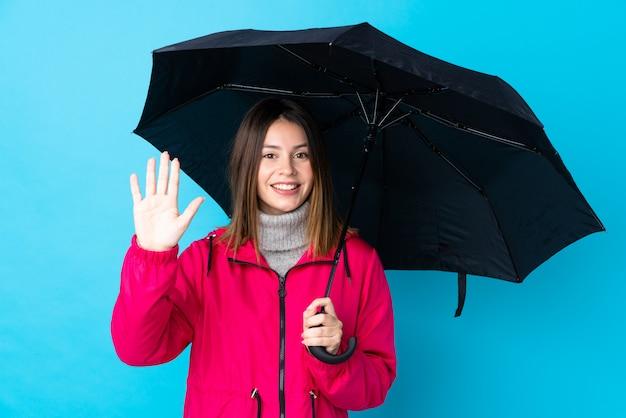Mulher segurando um guarda-chuva sobre parede azul isolada Foto Premium