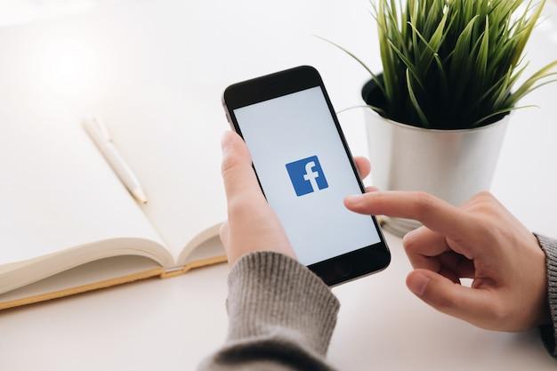 Mulher segurando um iphone 6s com serviço de internet social facebook na tela Foto Premium