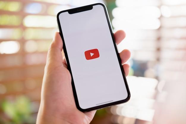 Mulher segurando um iphone x ou iphone 10 com serviço de internet social youtube na tela Foto Premium